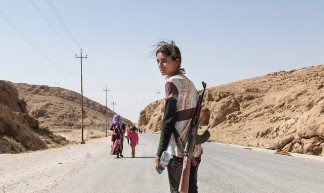 Yezidi girl carries an assault rifle to protect her family against ISIS - Adam Rifkin