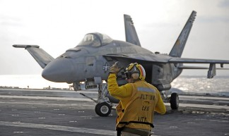 A Sailor directs an F/A-18E. - Official U.S. Navy Page