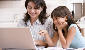 Woman and young girl in kitchen with laptop and paperwork smiling - GSCSNJ