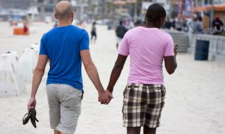 Gay couple holding hands on the beach - Nathan Rupert