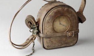 Prikklok van nachtwaker met leren omhulsel, riem en met sleutel aan ketting, gehaald uit puin 1940 - Museum Rotterdam