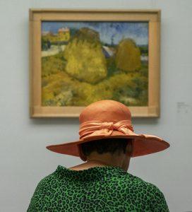 Vrouw met oranje hoed zit voor het schilderij 'Korenschoven in de Provence' van Vincent van Gogh. Foto van Maria Willems.