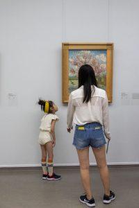 Moeder en dochter kijken naar de bloeiende perzikboom van Van Gogh. Foto van Maria Willems.