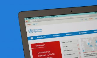 WHO World Health Organization website open on a computer screen with blue background - Jernej Furman